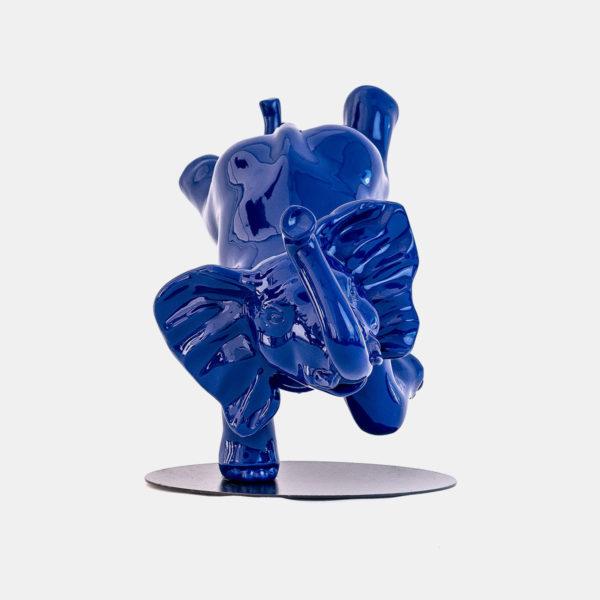 Elephant bleu sur une patte sur socle